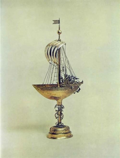 КУБОК-КОРАБЛЬ Ок. 1630 г. Нюрнберг. Мастер Исайя Цурлинден. работал в 1609-1632 гг. Серебро. Чеканка, литье, гравировка, золочение Высота 35.5 см. длина корпуса корабля 25 см Основное собрание музея Кубки-корабли получили большое распространение в XVI в. как своего рода отклик на великие географические открытия и успехи мореплавания. Они были сложны в исполнении, требуя тщательной, тонкой работы. Мастера стремились сделать кубок как бы миниатюрной моделью корабля, снабжая его соответствующей оснасткой; корабли имели полный такелаж, были вооружены, на палубе располагались воины. Сложная и неудобная для питья форма сосуда предполагала преимущественно декоративное его назначение в качестве настольного украшения или сравнительно редкое употребление в качестве кубка особого назначения. Вероятно, из него пили специально за здоровье и благополучие людей, которым предстояла поездка морем. В описании прощального приема, данного в 1598 г. Борисом Годуновым цесарскому послу Николаю Варкочу, говорится, что царь велел принести себе драгоценный сосуд в виде корабля и сказал: «Ты поедешь на корабле, а потому из корабля я пью твое здоровье и прошу Бога даровать тебе счастливого странствия» «Опись Московской Оружейной палаты», М.. 1884-1893. № I90I. табл.302 «Критико-литературное обозрение путешественников по России до [700 года и их сочинений Фридриха Аделунга».