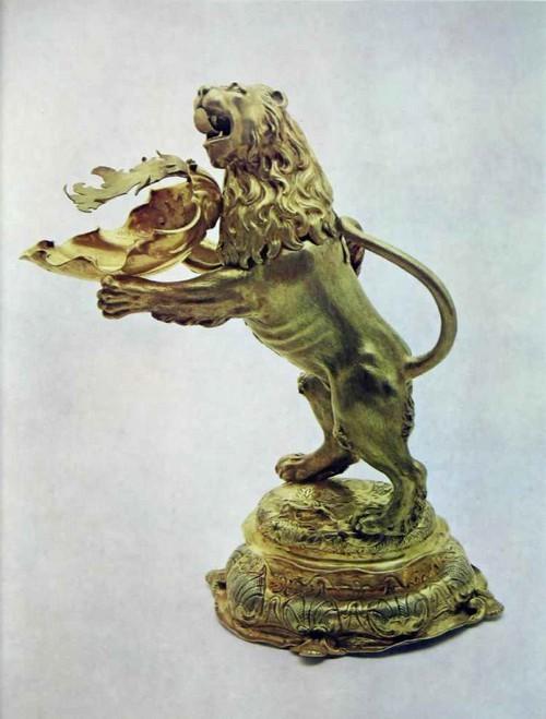 КУВШИН «ЛЕВ» До 1655 г. Аугсбург. Мастер с клеймом «Мельничное колесо», работал во второй трети 17 в. Серебро. Литье, чеканка, пуансон, золочение Высота 40 см Привезен в посольских дарах короля Швеции Карла X в 1655 г. Аугсбургские мастера барокко в своих фигурных сосудах особенно охотно обращались к мотивам живой природы. Различные растения, плоды и цветы, раковины улиток, фигуры животных и даже человека находили свое воплощение в старательно исполненных вазах, кувшинах и кубках. Излюбленной моделью в Аугсбурге на протяжении всего XVII в. был лев, стоящий или шагающий на задних лапах, иногда в короне и с атрибутами. Серебряную фигуру зверя со съемной головой мастера превращали в сосуд, настольное украшение или корпус часов. Лев анонимного мастера в коллекции Оружейной палаты - это своеобразный рукомойный кувшин. Чаша-раковина в лапах льва незаметно соединена с его туловищем, откуда поступала вода. Красиво декорируя слив, раковина, по существу, является носиком кувшина; вместе с тем она воспринимается как необходимый предмет-атрибут, несение которого предполагает сама поза шагающего льва с протянутыми вперед лапами. Мотив раковины, легко связывающийся в представлении человека с водой, был широко распространен в украшении предметов рукомойного гарнитура. Не случайно именно раковины вычеканены мастером в узоре на основании кувшина «Опись Московской Оружейной палаты, 1884-1893, № 1924. табл. зо8 F. Martin