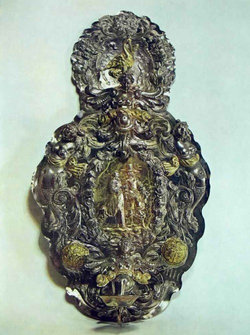 НАСТЕННЫЙ ПОДСВЕЧНИК 1655-1660 Аугсбург. Аноним HP Серебро. Чеканка, литье, золочение Размер 105 x59 см Привезен в дарах датского короля послом Гансом Ольделяндом ранее 1663 г. В пышном украшении серебряного блакера взгляд сразу выделяет в центре зеркала галантную сцену. Кавалер и дама в нарядных современных костюмах, беседуя, прогуливаются перед зрителем. Фигуры, обращенные друг к другу в трехчетвертном развороте, вычеканены тонко, с хорошим чувством линий Чистый гладкий фон позади пары полностью выявляет ее контуры, выгодно подчеркивает объемность рельефа, создает пространственную иллюзию. В исполнении фигур поражает мастерство чеканки, с помощью которой серебрянику удалось не просто передать в разнообразных подробностях костюмы персонажей, но и дать представление о тканях - плотном гладком шелке, легких ажурных кружевах