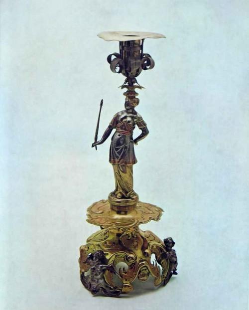 ПОДСВЕЧНИК 1649-1655 Гамбург. Мастер Генрих II Ламбрехт, работал в 1649-16б2 гг. Серебро. Литье, чеканка, золочение Высота 43 см Привезен в дарах от короля Швеции Карла X в 1655 г. царю Алексею Михайловичу Генрих II Ламбрехт - один из наиболее известных гамбургских златокузнецов. Его вещи закупались для шведской королевской сокровищницы, неоднократно присылались в составе посольских даров. В односвечном литом и чеканном настольном подсвечнике на высоком основании из причудливого прорезного кнорпеля несомненной удачей мастера является фигура богини. Грамотно моделированная, приятных пропорций, с изящным силуэтом, она не лишена своеобразной выразительности