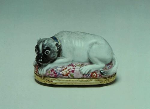 Табакерка Фарфор, в золотой оправе. Немецкая. Фарфор из Мейссена (Meissen), прибл. 1755 года, оправа того же времени. Вышина: 4.8 см. Длина: 8.2 см. Толщина: 4.6 см. К190е Сохранилось несколько мейссенских шкатулок в форме мопса. Эта собака приобрела особенное значение в Европе после того, как Римский папа воспретил католикам, в 1738 году, участие в масонских орденах. Вследствие этого запрета, многие из католическом знати объединились в ложи сходные с .масонскими, избрав себе символом именно мопса. В противоположность .масонам, они принимали и женщин в свои ложи. Посвященным в это общество вменялось в обязанность брать мопса на свои собрания, и коробка вроде настоящей выполняла это условие. Несомненно она служила и опознаванию ее обладателя перед другими членами Ордена Мопсов.