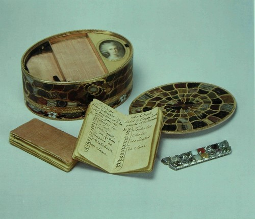 Табакерка Золото с вделанными полудрагоценными камнями; содержит миниатюру и платиновую полоску, обрамленную драгоценными камнями. Немецкая. Дрезден, прим. 1770-80 г. Работы, очевидно, Христиана Готлиба Штиля (Christian Gottlieb Stiehl) (1708-92 г.). Без пометки. Вышина: 3.7 см. Длина: 8.8 см. Толщина: 6.6 см. Это табакерка типа « штейн-кабинет » вроде той что была произведена в первый раз Нойбером (Neuber) (см. экспонат № 105), в которой использованы полудрагоценные камни из Саксонии в наибольшем, по возможности, количестве. Внутри находятся два рукописных каталога, один на французском языке а другой на немецком, перечисляющие все 180 использованных минералов соответственно их номерам. По извилистым кривым оправ можно предположить, что данная табакерка - изделие Штиля, скорее чем Нойбера, который предпочитал геометрические узоры.
