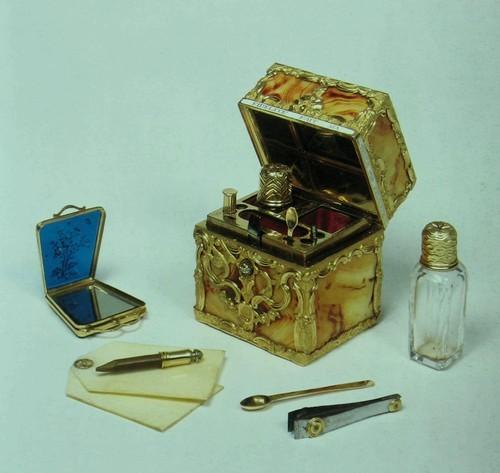 Несессер Агат в золотой оправе, с эмалью и нажимной кнопкой с бриллиантом. Английский. Около 1765 года. Без пометки. Вышина: 5.9 см. Ширина: 5.1 см. Толщина: 4.6 см. Kl67d Надпись, по-французски, гласит: L'ESPOIR DE ТА FIDELITE FAIT MA SEULE FEUdE (« Надежда на твою верность - это мое единственное счастье »). В несессере - пластинки из слоновой кости, два стеклянных флакона для духов, пилочка для ногтей и заодно щипчики, штопор с иглой, карандаш, ложка, инструмент для чистки зубов и ушей, и зеркальный ларец из синего стекла в золотой оправе. Несколько несессеров этой формы, обладающие достаточно схожими общими свойствами чтоб рассматривать их как производство одной и той же мастерской, известны в настоящее время (напр., в парижском музее Лувр имеются трое таковых). Неясно, однако, кто именно изготовил их.