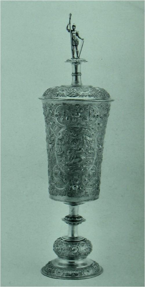Чарка, на длинном ножке Позолоченное серебро. Немецкий. Аугсбург, прибл. 1600. Изготовитель: Мельхиор Баир (Melchior Bair) (мастер с 1576 года, умер в 1634 году). Вышина: 50 см. Диаметр ножки: 12.2 см. К125Ь Сосуд такого типа был распространен в южной Германии, и в особенности в Аугсбурге, в конце шестнадцатого века. В настоящем изделии наблюдается хорошо известное чередование орнамента в виде завитков, гроздей фруктов, птиц и масок из шпатлевки, в перемежку с плоскостями покрытыми изображениями полулежачих животных на фоне скорей стандартизованных пейзажей. В данном случае, конь является зеркальным вариантом эстампа Йоста Аммана (Jost Amman) в его Thierbucli (Франкфурт, 1579), а олень заимствован из гравюры на дереве в книге Thierbuch (Цюрих, 1563).