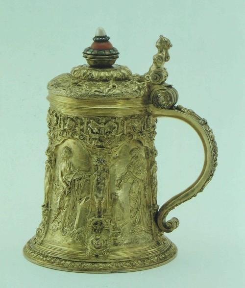 Кружка, пивная, высокая Позолоченное серебро, с прибавленным украшением из коралла с рубинами и изумрудами, а также с половиной жемчужины и бриллиантами. Немецкая. Нюрнберг, прибл. 1550 года. Изготовлена ювелиром из кружка Венцеля Ямницера (Wenzel Jamnitzer) Вышина: 17.5 см. Нижний диаметр; 12 см К122 Крышка - с чеканным изображением Похищения Европы и путешествия Посейдона по морю. Все поющие и играющие Музы по сторонам заимствованы от декоративных тарелок Петера Флетнера (Peter Flotner), известных из различных литейных изделий. Эти тарелки часто служили как модели для литья в мастерской выдающегося нюрнбергского ювелира Венцеля Ямницера, а также и другим мастерам, обрабатывавших различные материалы. Кружка эта находилась в Эрмитаже, в Ленинграде, но она была приобретена отцом барона до 1937 года.