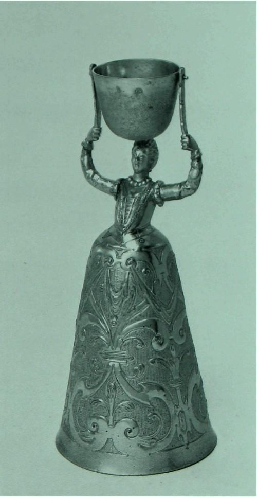 Кубок, подвижной Позолоченное серебро. Немецкий. Аугсбург, примерно 1630 г. Изготовитель: Якоб Гольгаген (Jakob Hollhagen) (мастер с прибл. 1627 года, умер в 1637 году). Вышина: 18.3 см. диаметр ободка: 7.8 см К161 Это - одна из разновидностей кубка предназначенного для игры, распространение которой приходится на вторую половину шестнадцатого века. Игра заключалась в следующем: дама держит высоко над собой .маленький кубок, подвешенный на горизонтальной оси, на которой он может вращаться. В этот кубок вливается жидкость с расчетом чтоб только затем она выливалась на юбку дамы. Не только в Германии, но и в Англии производились такие кубки, и их последние Аугсбургские образцы приходятся прибл. на 1650 год.