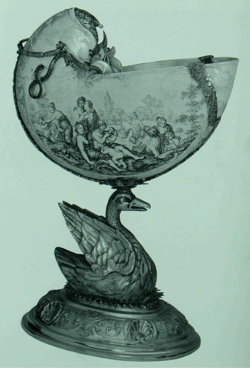 Кубок, ракушечный, формы лебедя Раковина Наутилуса оправленная в позолоченное серебро, с некоторыми деталями из эмалевой краски. Раковина выгравирована голландцем Корнелисом Белле- кином (Cornells Beltekm), прибл. в 1650-1675 годах; оправа - немецкая (Аугсбург?), 1710-1720 г. Высота: 28.8 см. База: 16 на 12.5 см. К170а Корнелис Беллекин, чья подпись поставлена на этой раковине, был выдающимся гравером и резчиком по раковинам; его настоящее изделие изображает, в изящной гризали с красноватыми оттенками, продвижение Нептуна и Амфитриона по волнам, и Вакханалию. Очень часто его раковины, которые были предназначены для горок коллекционеров, были оправлены намного позже их изготовления. В данном случае оправа особенно натуралистична.