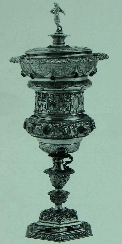 Кубок, крытый, на длинной ножке Позолоченное серебро, со вделанными гранатами. изумрудами, сапфирами и рубинами. Немецкий. Нюрнберг, прибл. 1565 г. Изготовитель: Файт Морингер (Veil Moringer) (мастер с 1535 года). Вышина: 35 см. Диаметр ножки: 11, 5 см. диаметр кромки: 13,1 см К194с Это - один из многих парадных, обрядовых кубков, сделанных в Гермаиии, в особенности в Аугсбурге и Нюрнберге в шестнадцатом веке и в начале семнадцатого века. Бордюр что вокруг середины чаши заимствован из мотива часто встречающегося в мастерской наиболее вьдающегося нюрнбергского ювелира того времени, Венцеля Ямницера (Wenzel Jamnitzer). В начале девятнадцатого века, кубок этот принадлежал одному из наиболее проницательных английских коллекционеров изделий раннего романтизма, Уилъяму Бекфорду (William Beckford), и по всей вероятности тогда же он был украшен драгоценными камнями.