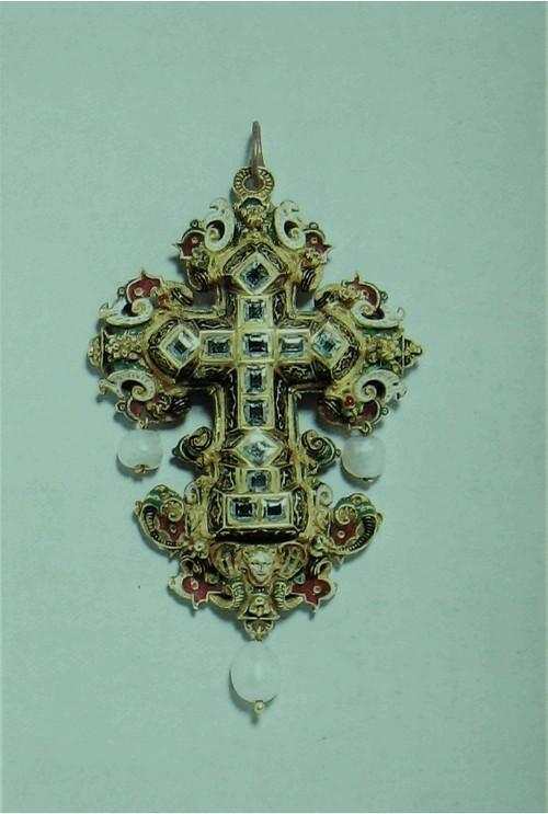 Брелок, крестообразный Эмалированное золото, со вделанными бриллиантами и с подвешенными жемчужинами. Повидимому южно-германский, третьей четверти шестнадцатого столетия. Высота: 7 см. Ширина; 4.9 см. К134Ь Конструкция этого изделия типична для .метода выработанного по-видимому в Мюнхене и Аугсбурге, и применявшегося между прибл. 1550 и 1580 годами. Он охарактеризован литьевым орнаментом, переплетающимся или же в виде завитков, обычно с фигурками или гроздями фруктов или масок. Драгоценные камни составляют отдельный элемент, нередко с эмалировкой выдержан - ной в мавританском стиле по сторонам глубоких оправок, а тыловая сторона покрыта отдельной, слегка выпуклой пластинкой.