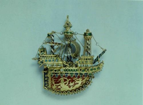 Брелок формы корабля Эмалированное золото, со вделанными жемчугами. Район Средиземного моря, вторая половина шестнадцатого столетия. Корпус заменен в восемнадцатом веке, по всей вероятности ювелиром - изготовителем шкатулок. Вышина, без кольца для подвешивания: 7.5 см. Длина: 7 см. K127h Хотя несомненно что художник не намеревался дать реалистическое изображение корабля той эпохи, он все же достаточно точно воспроизвел его характерные черты чтоб можно было заключить что это скорее галеон чем карак. Филигранная эмаль, как та что в данном образце, производилась во многих местах, в том числе в Испании, Италии, на берегах Адриатического и Эгейского морей, и в Центральной Европе, в особенности в Венгрии. Брелки формы корабля пользовались успехом в конце шестнадцатого века, и еще производились в районе Эгейского моря в восемнадцатом столеТИИ