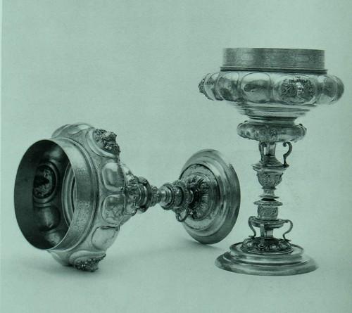 Кубок, двойной, на длинной ножке Позолоченное серебро Немецкий. Аугсбург, прибл. 1565 года. Пометка изготовителя не отождествлена: изображение дома. Вышина: 58 см. Диаметр ножки: 14.5 см KI42 Двойные кубки были распространены в Германии от пятнадцатого по семнадцатый век, как подарки в торжественных обстоятельствах, и поэтому они бывали зачастую величественного творческого замысла. Они cчитaлиcь особенно подходящими для свадебного подарка в связи с тем, что две одинаковые их половины сочетаются в единое целое. Разновидность этих кубков, в которой - как в настоящем - наблюдается разделение на доли, происходит из Нюрнберга, но оно распространилось главным образом из Ayгсбурга в конце шестнадцатого столетия. Как и кубок № 5, так и этот принадлежал в семнадцатом веке графу Ласло Ракоци де Фельшё Вадац (Ladislaus Rakoszy de Felso Vadacz) (умер в 1644 году) и графине Эржебет Банфи де Наджь (Erzsebet Banffy de Nagy), инициалы которых находятся на двух долях каждого из этих кубков.