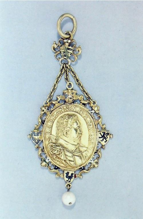 Брелок с медалью Эмалированное золото Немецкий (Саксония), датирован 1604 годом. Вышина: 10 см. Ширина: 4.7 см. К138 Медаль была выбита в 1603 году, чтоб отметить раздел Саксонии между герцогом Иоганном цу Сак- сен-Веймар и детьми его старшего брата, Фридриха Вильгельма в Саксен-Веймаре и Саксен-Альтенбурге. Герцог Иоганн изображен на лицевой стороне, а его жена, Доротеа Мария из Ангальта, на оборотной стороне. Геральдический герб показывает территории подчиненные династиям Саксонии и Ангальта. Медали смонтированные в брелки были специфически немецким изделием; они выдавались принцами и сановниками как знак почтения важным гостям, и как награда нотаблям и подданным.