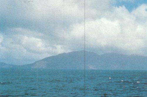 Во время шторма волны бьются о высокие, в несколько сотен метров, утесы окутанного облаками острова.