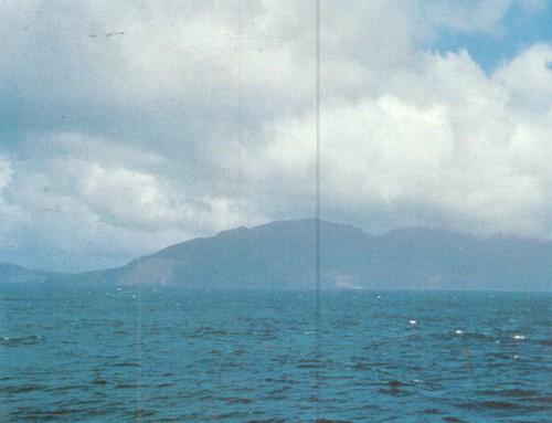 Остров Гоф. Во время шторма волны бьются о высокие, в несколько сотен метров, утесы окутанного облаками острова.